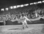 Lefty Grove, Red Sox pitcher, warms up in front of stands at Fenway