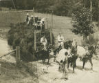 """Farmerettes"" bringing in fully loaded hay wagon pulled by four draft horses on..."